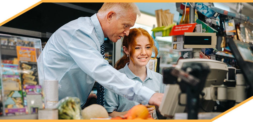 Supervisor instructs employee at grocery store checkout