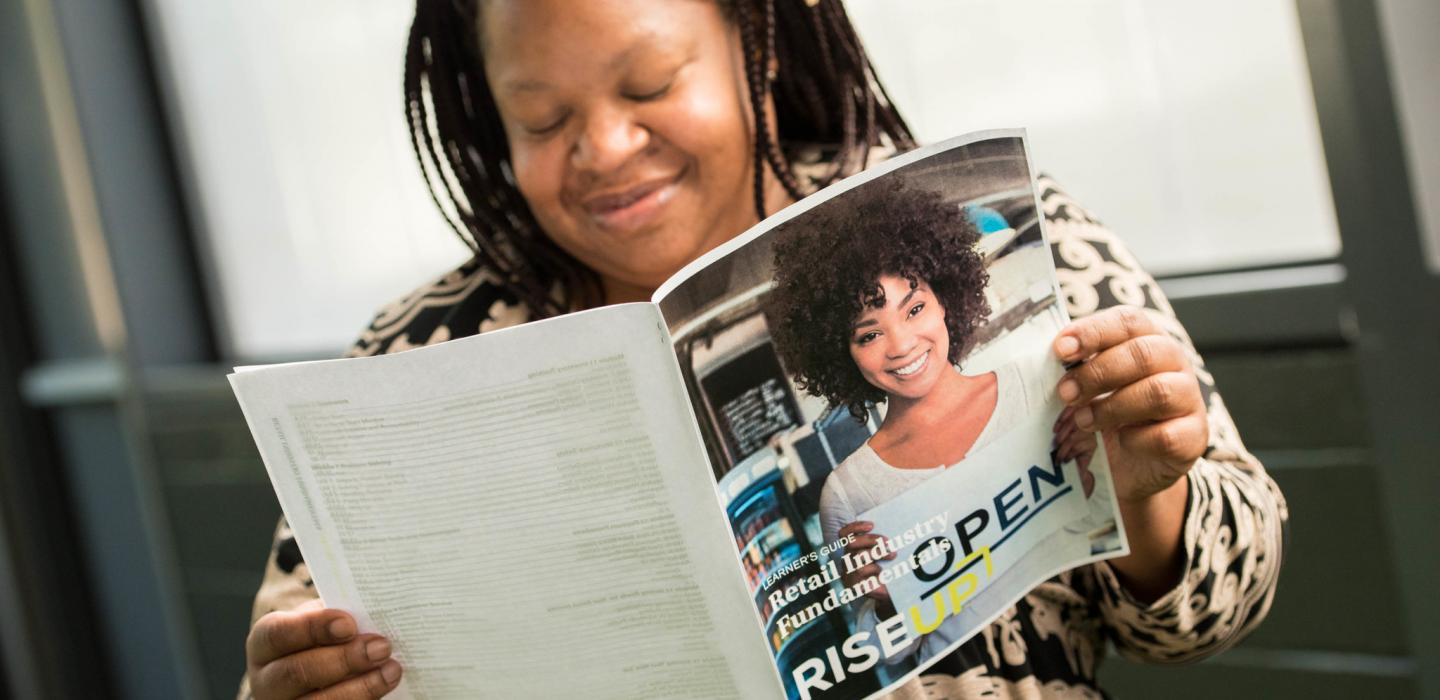 RISE Up learner reading a RISE Up brochure