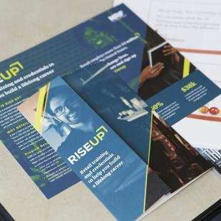 A RISE Up brochure on a table