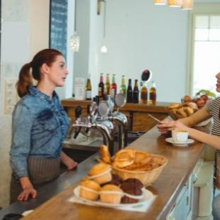A customer and an employee at the counter at a cafe