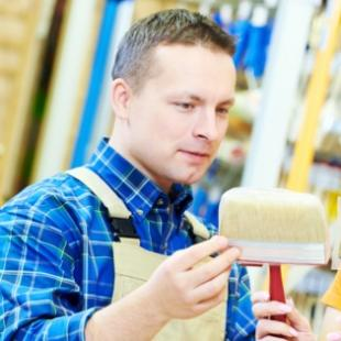 A male employee assisting a female customer select paintbrushes in a hardware store