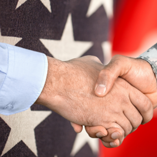 A military man shaking another man's hand in front of the American flag