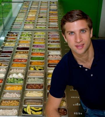 Matthew Corrin, the founder and CEO of Freshii, with an array of fresh vegetables