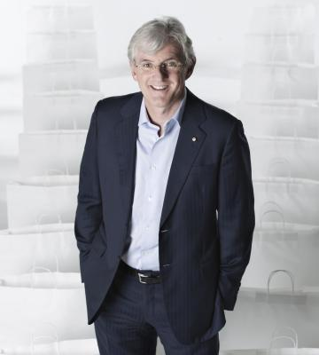 A headshot of Steven Lowy, a Co-CEO of Westfield Corporation, in a sea of white shopping bags