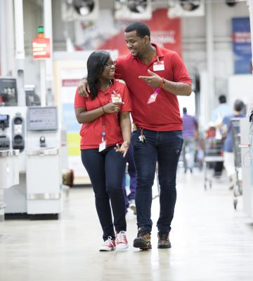 Two BJ's Wholesale Club employees walking in a BJ's location