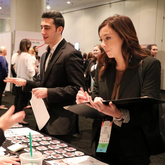 a guy and a girl set of students talking to a lady at the student program career fair 2018