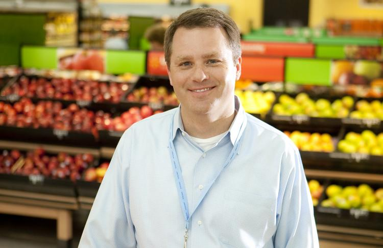 Doug McMillon, the President and Chief Executive of Walmart, amongst produce